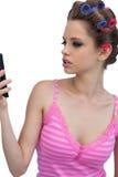 Modellera bärande hårrullar som poserar se telefonen Royaltyfri Bild