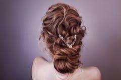 Modellera den blonda kvinnan med den perfekta frisyren och den idérika hår-klänningen, baksidasikt Arkivbilder