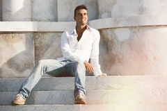 Modellera den stiliga mannen kopplat av sammanträde på momenten av vit marmor arkivfoto