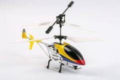 Modellera denkontrollerade helikoptern med fjärrkontroll Gjort av metallkropp, med plast- gul, blå och röd färg för blad, isolat arkivfoto