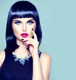 Modellera flickan med den moderiktiga fransfrisyren, makeup och manikyr arkivfoton