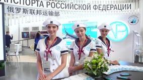 Modellera flickor poserar mot bakgrunden av st?llningen av det fr?n den ryska federationen departementet av transport arkivfilmer