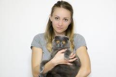 Modellera fotoet tagna närbilden till midjan, modell rymmer en katt i hennes armar royaltyfria bilder