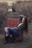 Modellera i en parkera med en gammal stol Fotografering för Bildbyråer