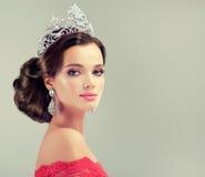 Modellera i ett delikat smink som är iklätt en röd kappa och krona Royaltyfri Foto