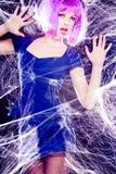 Modellera med den purpurfärgade wigen och intensiva sminket som fångas i en spindelrengöringsduk Royaltyfri Fotografi