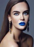 Modellera med färgrik makeup med blåa kanter och smycken Royaltyfri Foto