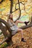Modellera med långa ben som sitter på ett träd Iklätt en ljus klänning Arkivbilder