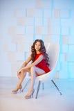 Modellera med långt hår i röd klänning med stol Vågkrullning Hairst Royaltyfria Bilder