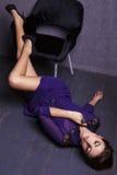 Modellera med mörkt hår i den eleganta klänningen som ligger på det wood golvet arkivfoton