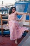 Modellera på havet i vinter, med långt le för rosa färgklänning royaltyfria bilder