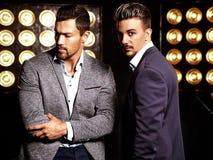 Modellerar den sexiga stiliga mannen för mode två iklädda eleganta dräkter för män royaltyfri foto