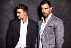 Modellerar den sexiga stiliga mannen för mode två iklädda eleganta dräkter för män arkivfoton