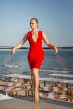 Modellerar det attraktiva barnet i ljus röd klänning poserar på en blå havsbakgrund Charmig flicka med den perfekta kroppen nära  Royaltyfri Fotografi