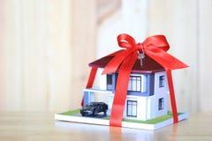 Modellerar det nya hem- begreppet för fastigheten och för gåvan, huset med röd ribbo royaltyfri fotografi