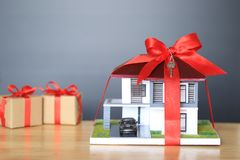 Modellerar det nya hem- begreppet för fastigheten och för gåvan, huset med det röda bandet och tangent på svart bakgrund arkivfoto