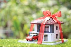 Modellerar det nya hemmet f?r g?van och fastighetbegreppet, huset med det r?da bandet och bilen p? naturlig gr?n bakgrund royaltyfria bilder