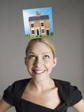 Modellhem överst av ung kvinnas head föreställande homeownership Arkivfoton