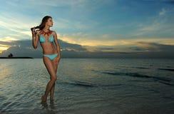 Modelli in bikini con la posa della collana di corallo sexy sulla spiaggia vuota immagine stock libera da diritti