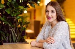 Modelli con capelli lunghi biondi e rossetto rosa luminoso in maglione bianco che si siede su una sedia in un caffè con il bello  Fotografia Stock