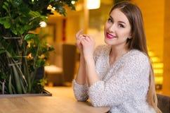 Modelli con capelli lunghi biondi e rossetto rosa luminoso in maglione bianco che si siede su una sedia in un caffè con il bello  Immagini Stock