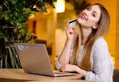 Modelli con capelli lunghi biondi e rossetto rosa luminoso in maglione bianco che si siede su una sedia in un caffè con il bello  Fotografia Stock Libera da Diritti
