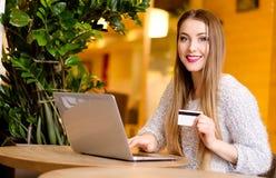 Modelli con capelli lunghi biondi e rossetto rosa luminoso in maglione bianco che si siede su una sedia in un caffè con il bello  Immagine Stock