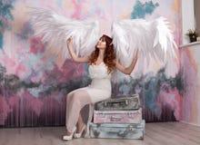 Modelli con le ali aperte di angelo che si siedono sulle retro borse Fotografia Stock