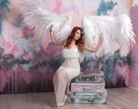Modelli con le ali aperte di angelo che si siedono sulle retro borse Immagine Stock