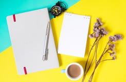 Modelli del fondo con lo spazio in bianco del testo su carta per appunti del libro e fiori, sveglia e tazze da caffè secchi decor fotografia stock