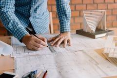 Modelli dell'architetto o di ingegneria e matita d'esame di tenuta immagine stock