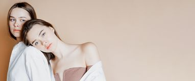 Modelli di bellezza di modo due ragazze nude dei gemelli delle sorelle belle isolate su fondo beige, insegna immagine stock