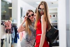 Modelli femminili attraenti che annunciano la nuova raccolta degli occhiali da sole di estate nel deposito di modo Immagine Stock Libera da Diritti