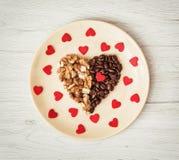 Modelli il cuore dei chicchi di caffè e delle noci sbucciate con molti piccoli Immagine Stock
