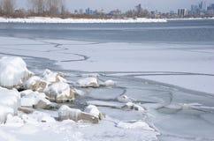 Modelli nel ghiaccio della riva e nell'orizzonte della città del lago Fotografie Stock Libere da Diritti
