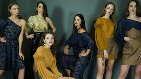 Modelli professionali con trucco perfetto che posa in vestiti alla moda sulla parete del fondo archivi video