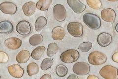 Modelli senza cuciture delle pietre sul pavimento del cemento per struttura del fondo Immagine Stock