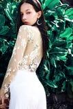 Modellieren Sie mit dem dunklen langen Haar in den klassischen Hosen des Breitbeines, die nahe grünen tropischen exotischen Blätt Stockfotografie