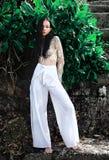 Modellieren Sie mit dem dunklen langen Haar in den klassischen Hosen des Breitbeines, die nahe grünen tropischen exotischen Blätt Stockbild