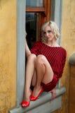 Modellieren Sie mit schwarzem und rotem gestreiftem Schlägerflügel-Strickjackenkleid Stockfotografie