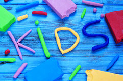 Modelling clay of different colors forming the word kids Stock Images