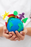 Modelling clay earth with rainbow and trees in child hands stock photo