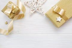 Modelljul stjärna och guldgåvaband som är flatlay på en vit träbakgrund, med stället för din text Arkivfoto