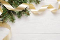 Modelljulgran- och guldband som är flatlay på en vit träbakgrund, med stället för din text Fotografering för Bildbyråer