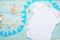 Modelllägenheten lägger vit behandla som ett barn Bodysuitskjortan på en blå lantlig träbakgrund med det nautiska snäckskalet, sn arkivfoton