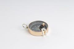 Modellminiatur auf Kompass auf Weißrückseitenboden Lizenzfreie Stockfotografie