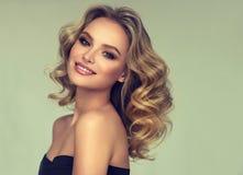 Modello abbastanza biondo-dai capelli con l'acconciatura riccia e sciolta ed il trucco attraente fotografie stock