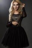 Modello affascinante in vestito nero e elegante fotografia stock