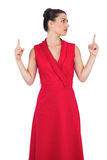 Modello affascinante in vestito rosso che indica su Fotografia Stock