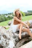Modello alla moda della donna del cowgirl all'aperto su un tronco di albero Immagine Stock